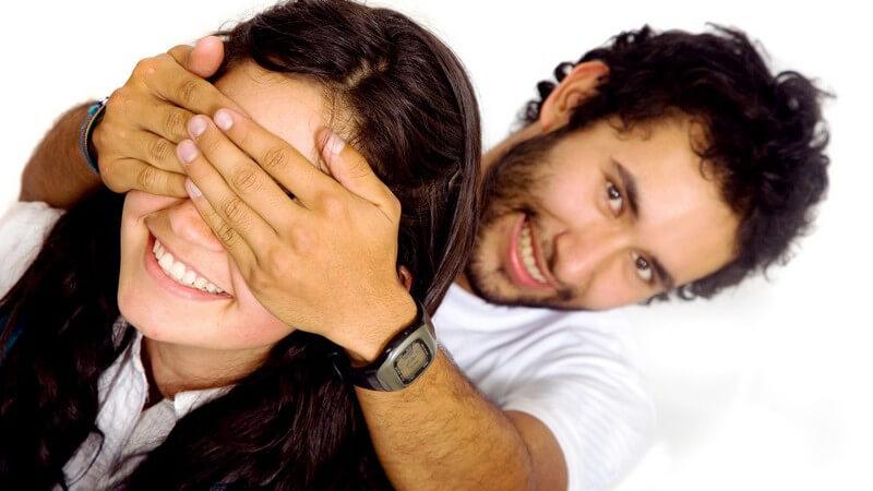 Junges Paar, er überrascht sie von hinten und hält ihr die Augen zu