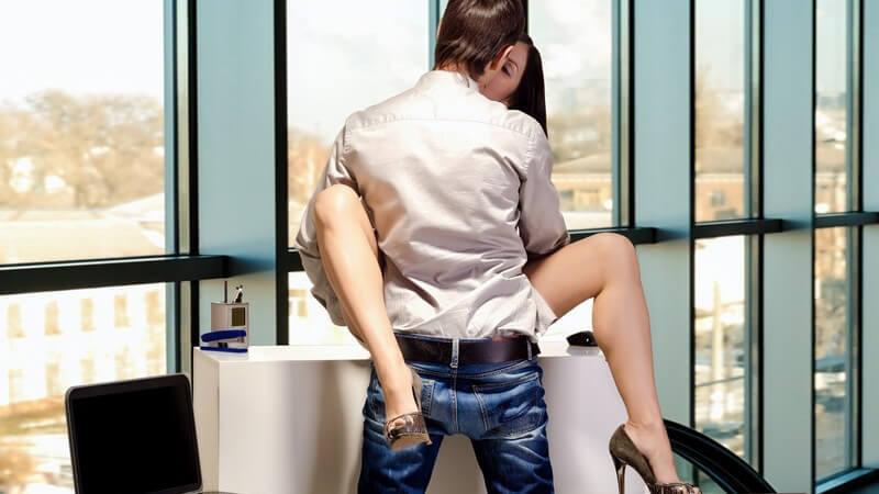 Paar beim Sex auf einem Schreibtisch in gläsernem Büro