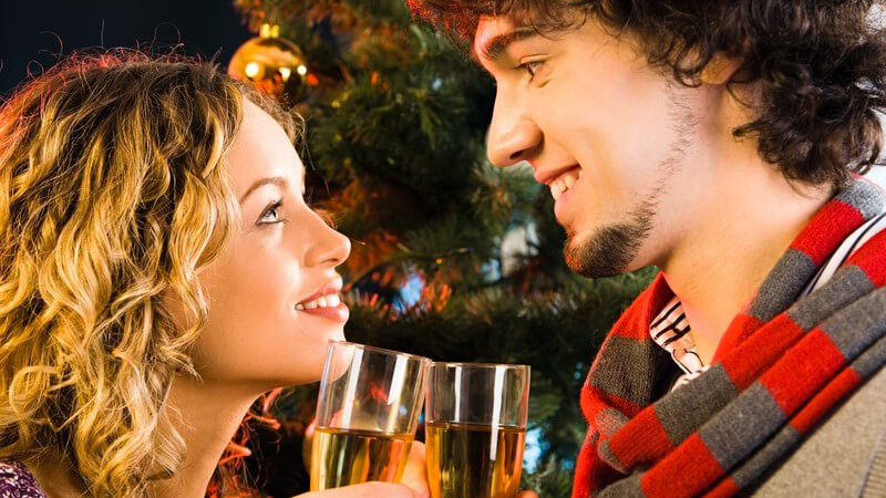 Junges Paar steht am Weihnachtsbaum, sie schauen sich lächelnd ins Gesicht und stoßen an
