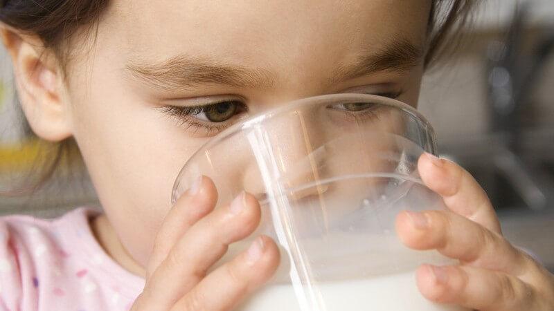 Kleines Mädchen trinkt Milch aus Glas