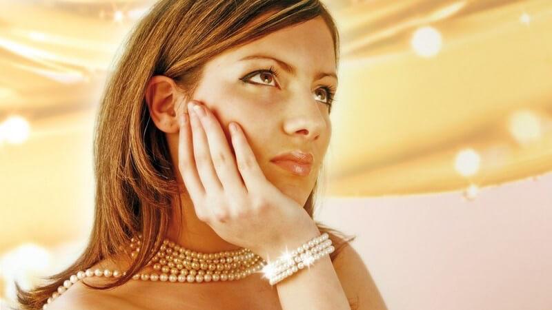 Kopf- und Schulterpartie einer unbekleideten, traurigen jungen Frau mit Perlenschmuck, in Gold gehalten