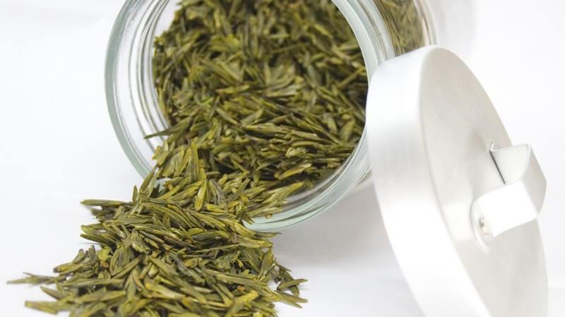 Umgekippter Glasbehälter mit grünem, losen Tee auf weißem Hintergrund