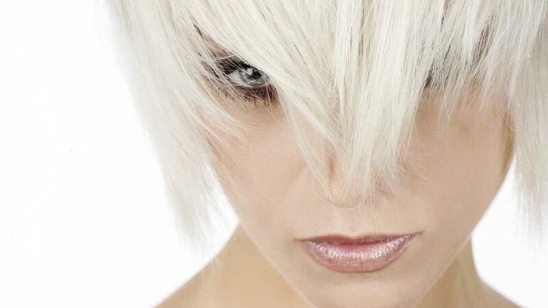 Aschblonde Kurzhaarfrisur verdeckt Auge und Nase einer jungen Frau