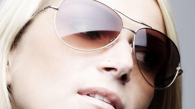Blonde junge Frau mit großer Sonnenbrille auf grauem Hintergrund
