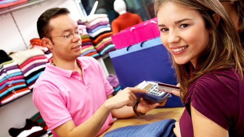 Junge Frau an Kasse einer Boutique reicht Kassierer Karte zum Bezahlen