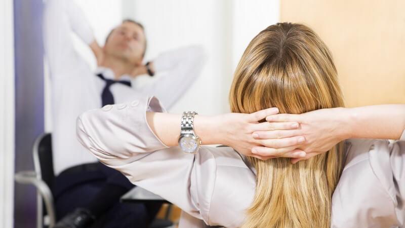 Frau und Mann im Büro sitzend, die Hände hinter den Kopf verschränkt