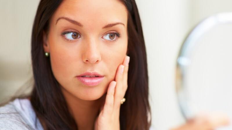 Junge Frau schaut in Kosmetikstudio, streicht sich über die Wange