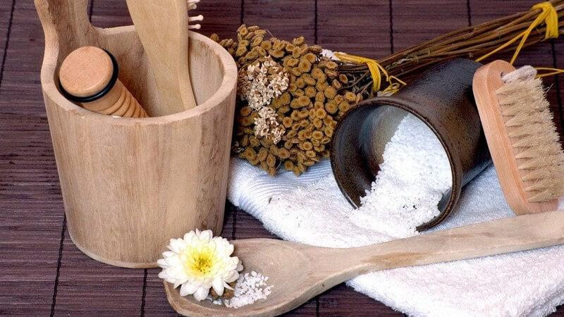 Sauna-Set auf dunklem Holzboden mit Bottich, Bürste, Holzlöffel, Saunasalz, weißem Handtuch, Massagebürste und Zweigen