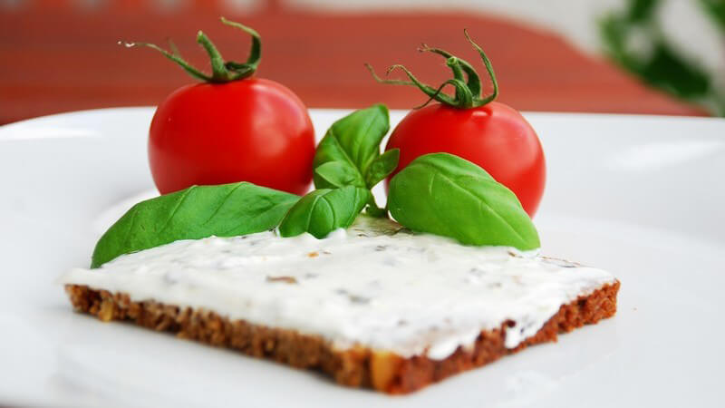 Scheibe Brot mit Frischkäse, dahinter frische Tomaten und Basilikum