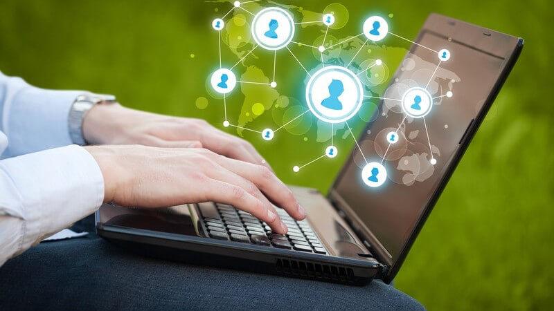 Hände auf Tastatur eines Laptops, über dem vernetzte Social Media-Avatare schweben, grüner Hintergrund
