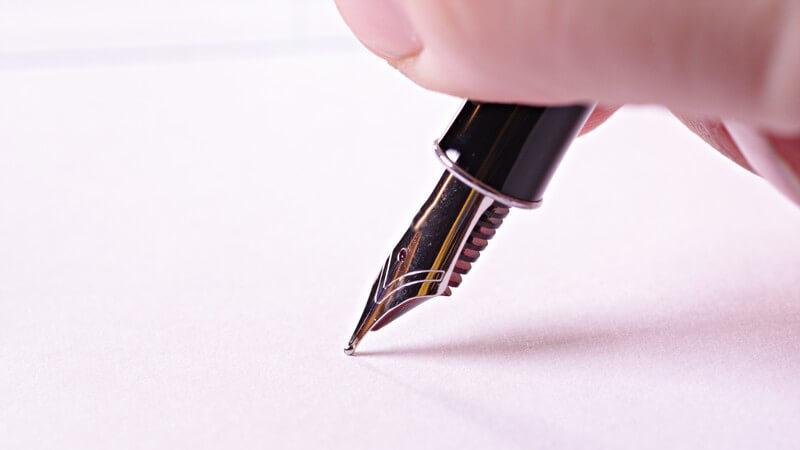 Schwarzer Füllfederhalter, von Fingern gehalten auf weißem Papier