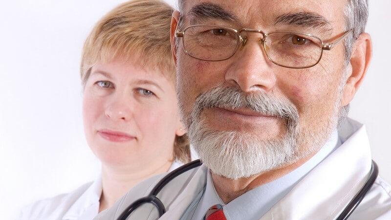 Portrait eines Arztes, Arme vor Brust verschränkt, im Hintergrund Krankenschwester