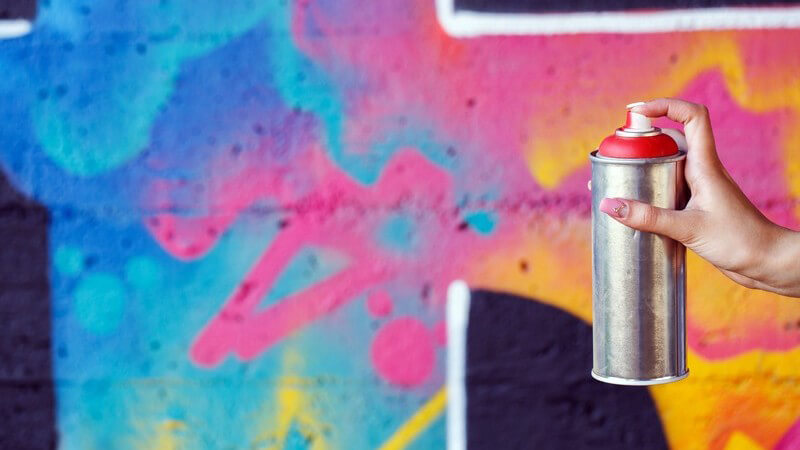 Hand einer Frau hält Sprühdose, im Hintergrund Graffitibild auf Mauer