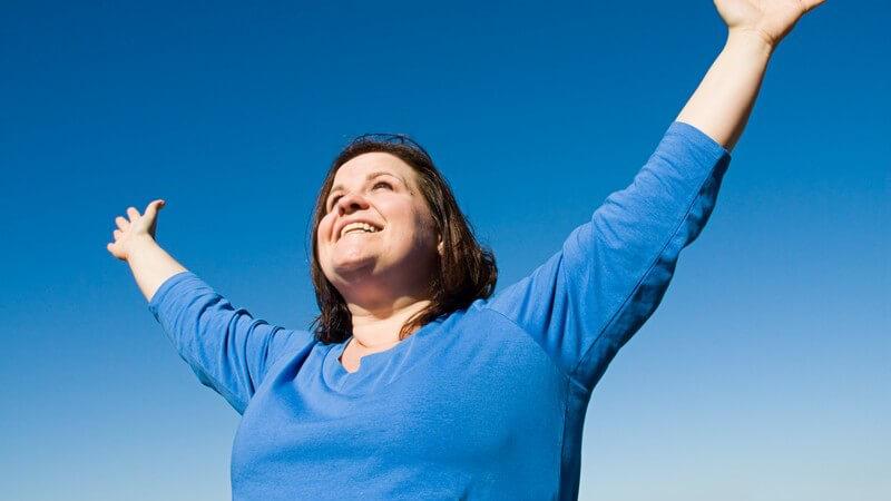 Übergewichtige Frau streckt lächelnd beide Arme in den Himmel