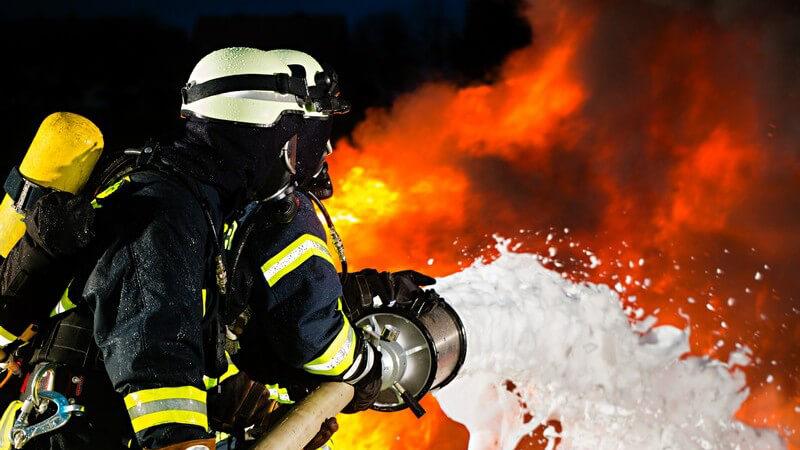 Feuerwehrmann löscht Feuer, Brand mit Schlauch