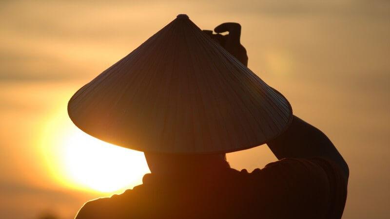 Mann mit vietnamesischem, spitzen Hut im Sonnenuntergang