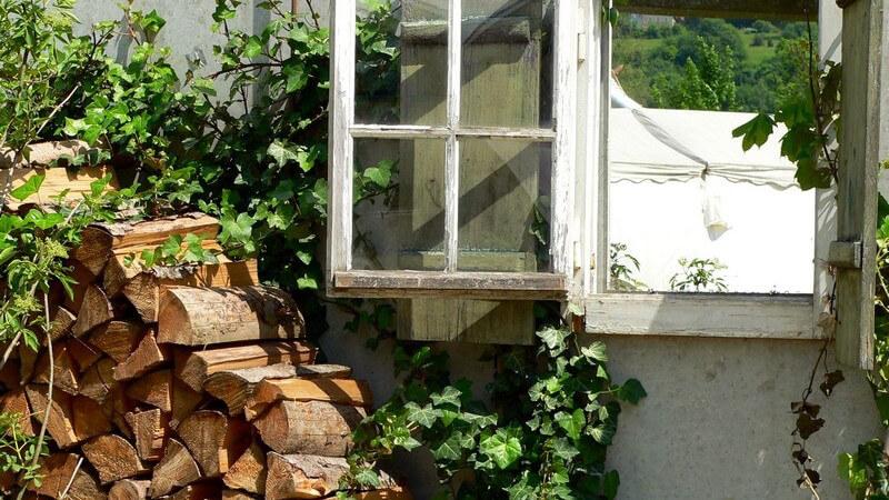 Offenes Fenster in Hof, davor gestapeltes Brennholz