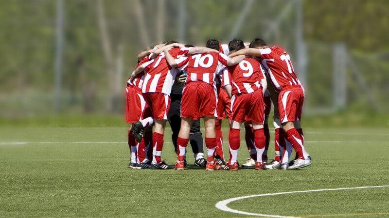 Fußballteam in roten Trikots im Kreis auf Fußballfeld