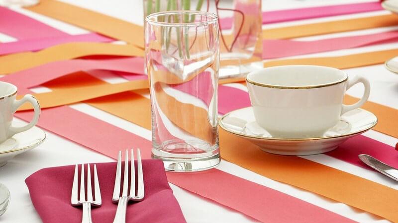 Gedeckter Tisch mit rosanen und orangen Farben, pinke Blumen in Vase