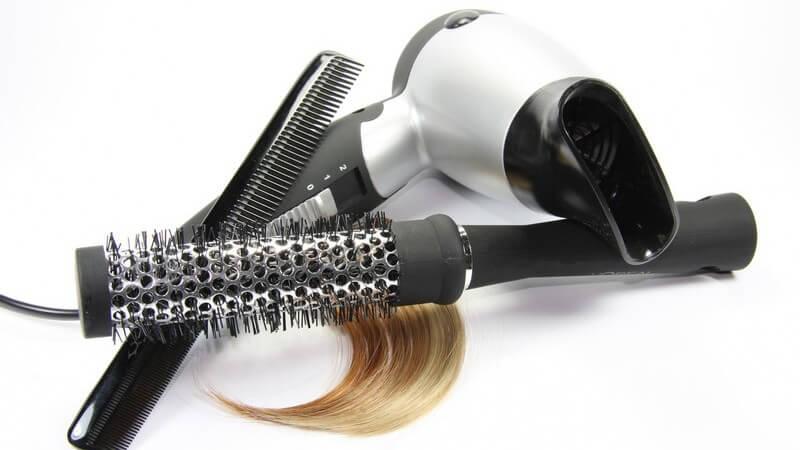 Rundbürste, Föhn, Kamm, Haarsträhne auf weißem Hintergrund