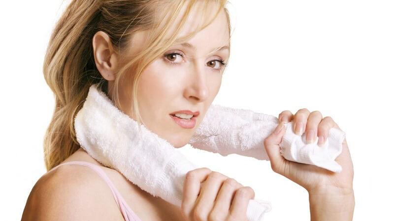 Erschöpfte Sportlerin hält sich ein weißes Handtuch um den Hals