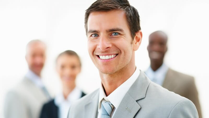 Junger Geschäftsmann mit Kollegen im Hintergrund lächelt in Kamera