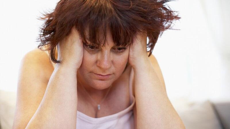 Unglückliche übergewichtige Frau fasst sich an den Kopf