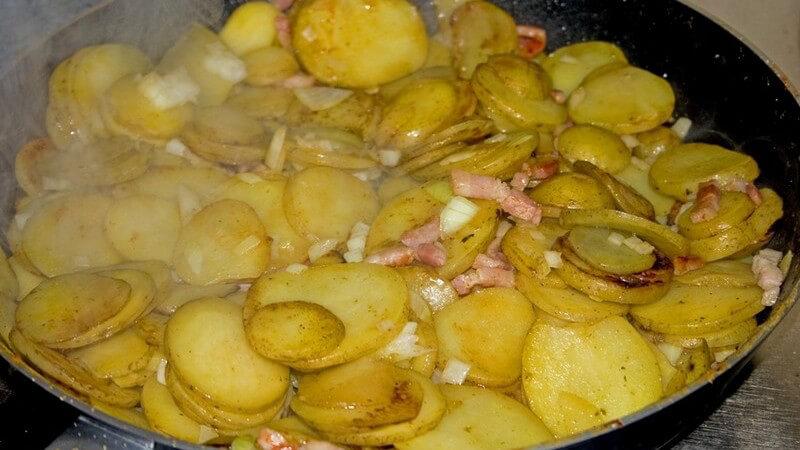 Nahaufnahme von Bratpfanne mit frischem, dampfenden Bauernfrühstück, Bratkartoffeln, Zwiebeln, Speck