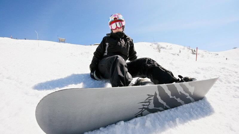 Snowboarder sitzt auf Skipiste unter blauem Himmel