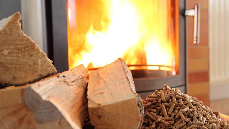Kaminfeuer im Kaminofen, davor Holzpellets und Kaminholz