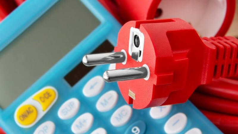 Roter Stromstecker auf blauem Taschenrechner