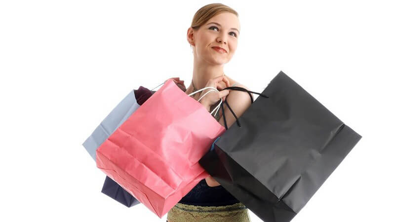 Junge Frau schaut glücklich nach oben, trägt vier Einkaufstaschen vom Einkaufen und Shoppen bei sich, weißer Hintergrund