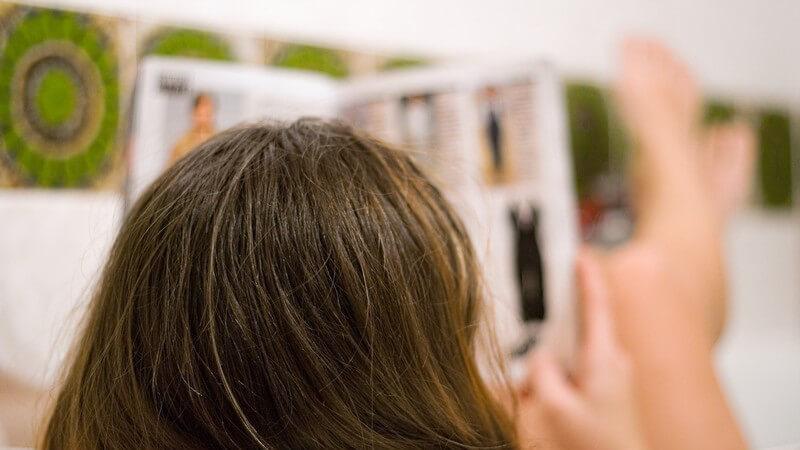 Hinterkopf einer Frau, sie liegt in der Badewanne und liest eine Zeitschrift