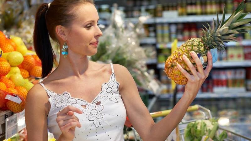 Junge dunkelhaarige Frau im Supermarkt hält Ananas in der Hand