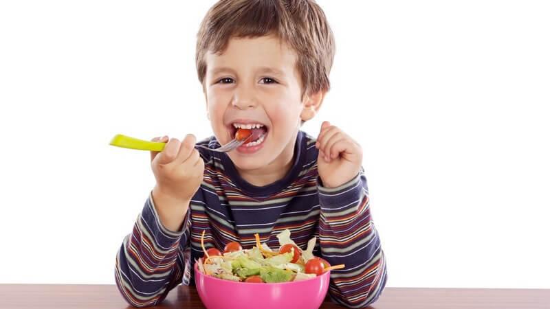 Kleiner Junge sitzt am Tisch und isst frischen Salat