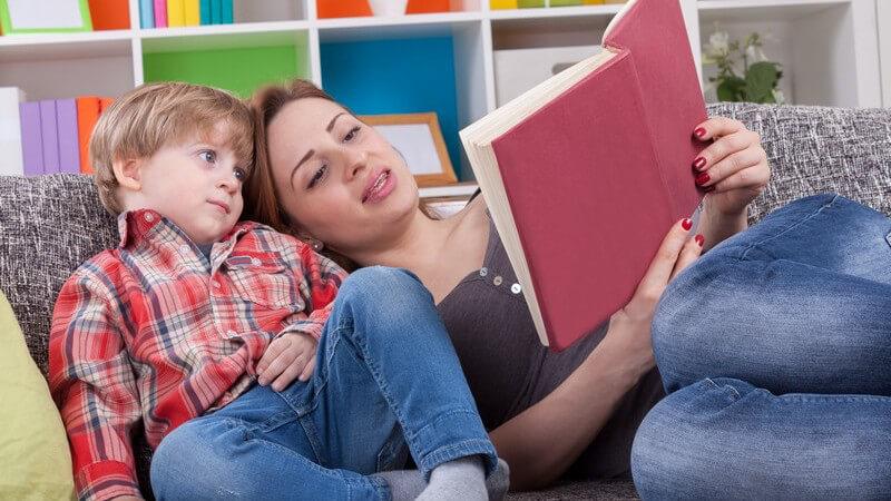 Vorlesen: Mutter mit Sohn auf der Couch, sie liest ihm etwas vor