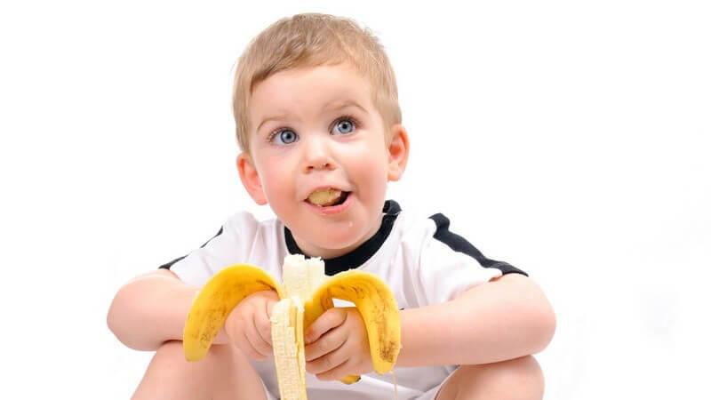 Kleinkind isst Banane und schaut nach oben
