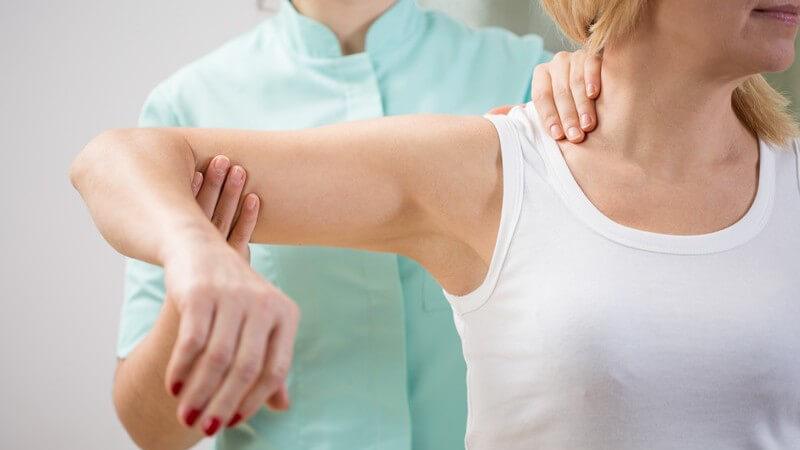 Physiotherapeut in grün untersucht eine Patientin an der Schulter, den rechten Arm ausgestreckt