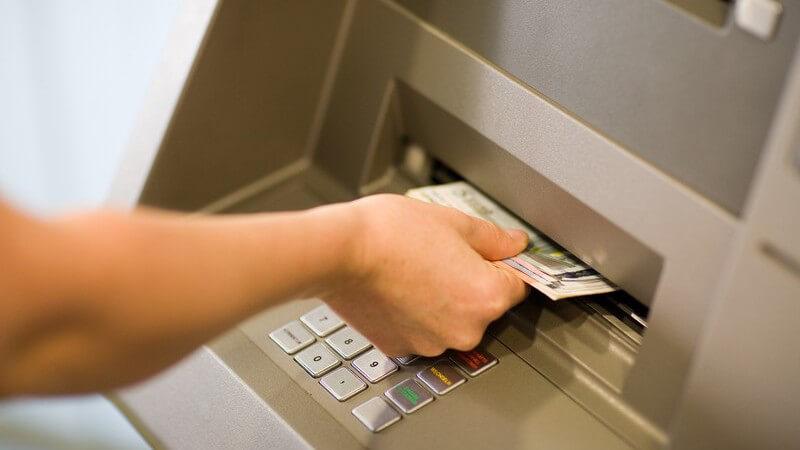 Rechte Hand zieht Geld aus Geldautomat heraus