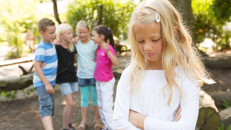 Mädchen mit verschränkten Armen und Schmollmund, im Hintergrund lästern vier Kinder