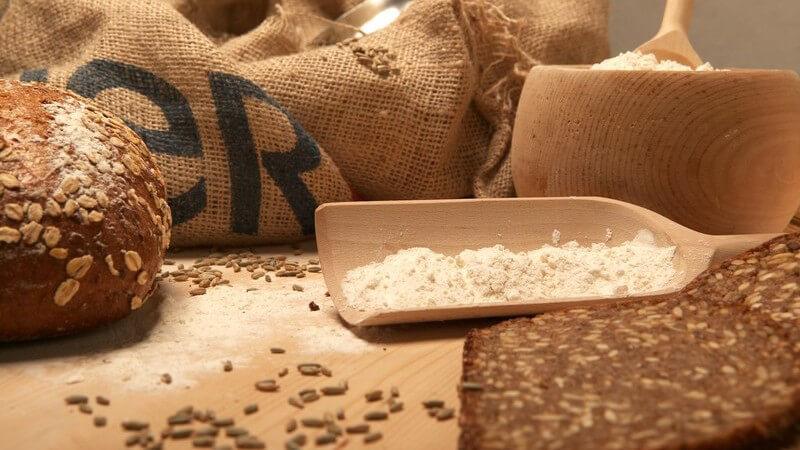 Säcke mit Getreide, Brot, teils geschnitten, Mehl auf Holzbrett