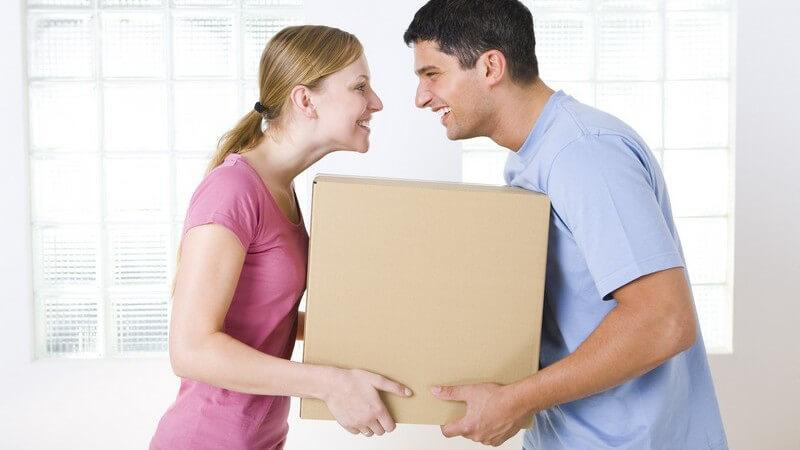 Junges Paar beim Umzug, tragen zusammen Karton und lachen sich an