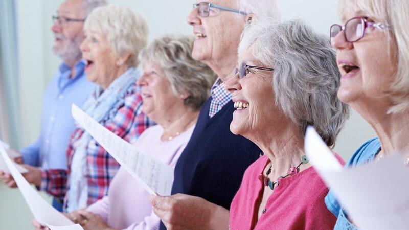 Sechs Senioren halten Notenblätter und singen fröhlich im Chor