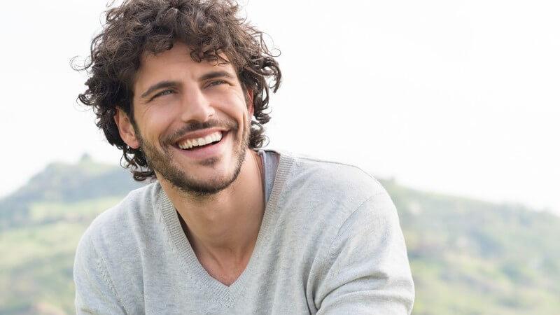 Lächelnder Mann mit Bart und langen braunen Locken in grauem V-Pullover