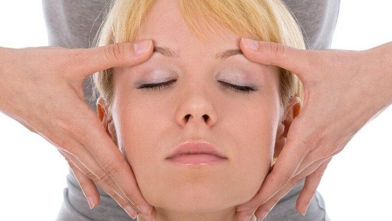 Frauengesicht einer blonden Frau, die eine dahinter stehenden Frau mit Händen an Schläfen massiert (Kopfmassage)