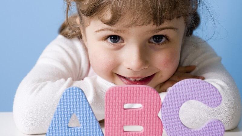 Kleines Mädchen auf Arme gestützt, vor ihr die Buchstaben ABC