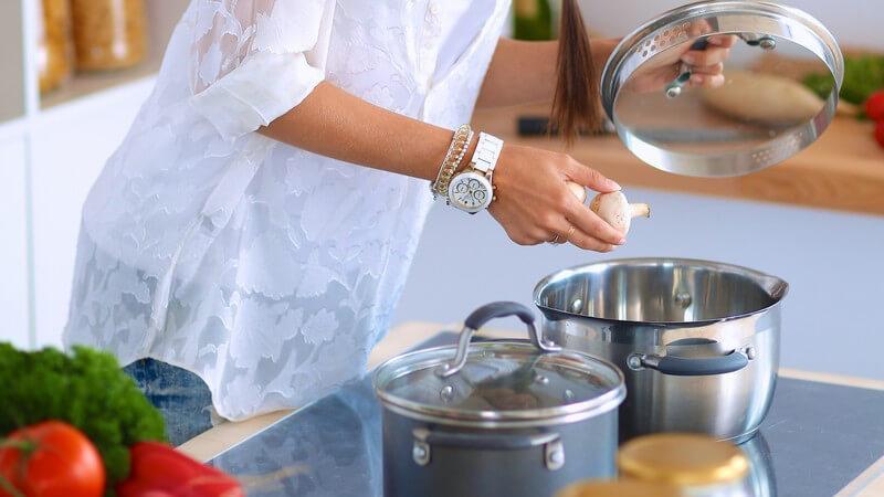 Frau in weißer Bluse beim Kochen, hebt den Deckel vom Topf und gibt Pilze hinein