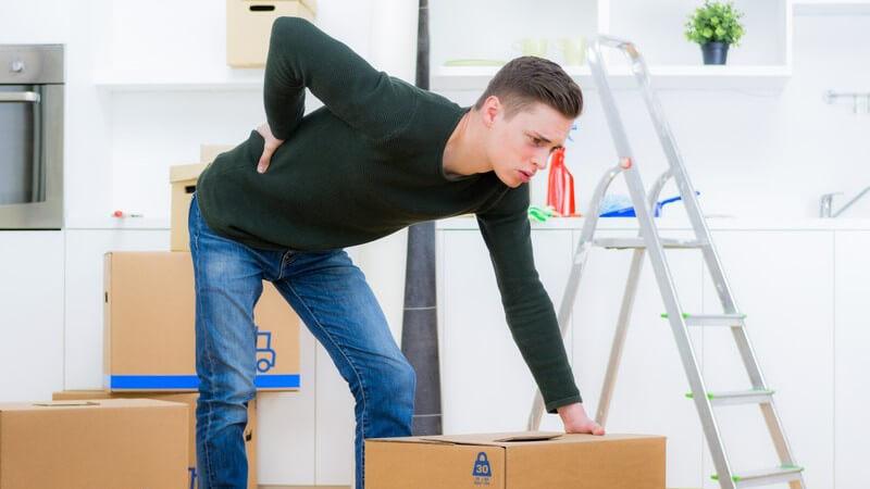 Junger Mann in dunklem Pullover und Jeans stützt sich vor Rückenschmerzen auf einen Umzugskarton