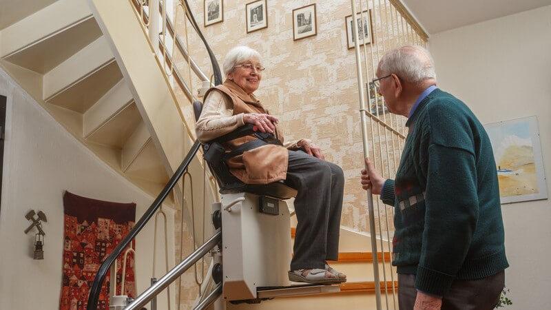 Senioren-Paar im Treppenhaus seines Zuhauses, Frau sitzt auf dem Treppenlift