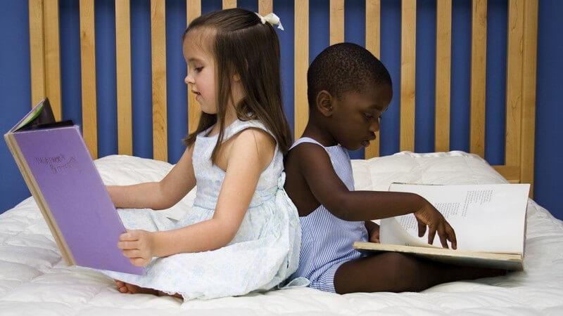 Zwei Kinder lesen in Büchern, ein hellhäutiges, brünettes Mädchen links und ein farbiger Junge in blauem Shirt rechts